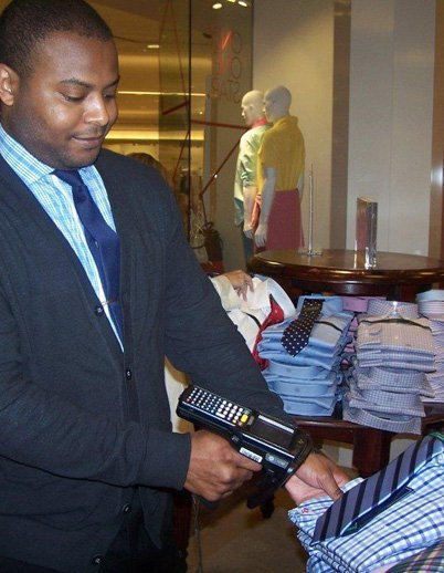 MACY'S RFID:  Macy's rolled out RFID to all of its stores. Above, a Macy's file photo of a Macy's clerk working with an RFID reader. Photo courtesy of Macy's.