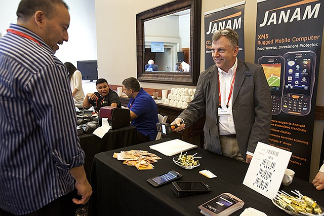 SCAN MAN: Janam showing an attendee how their scanners work and what their booth is all about.