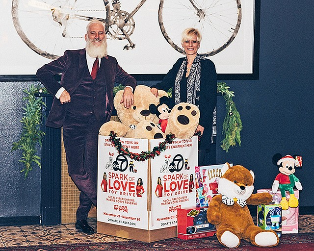 Fashion Santa and Celeste Boehm, UBM vice president of retail engagement, with toys collected for Spark of Love