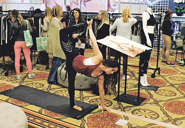 A yogi strikes a post at the Alo Yoga booth at Active Collective in Huntington Beach, Calif. The trade show was held concurrently with its sister show, Swim Collective.