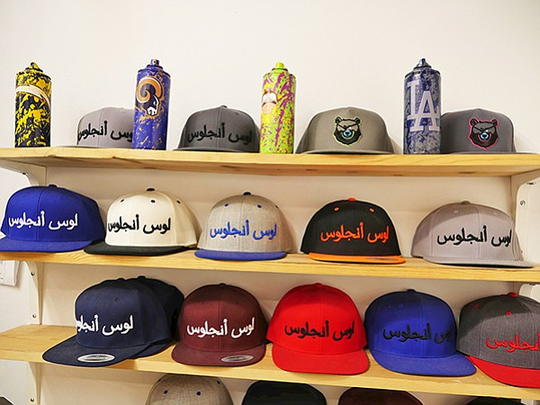 "Raised in Los Angeles-brand caps with Arabic script spelling out the words ""Los Angeles"""