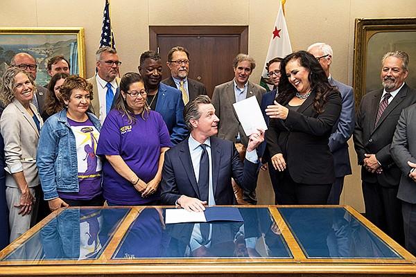 California Governor Gavin Newsom signs AB 5 on Sept 18.