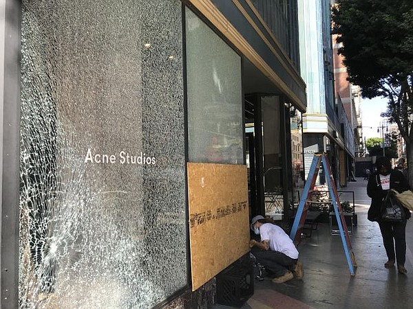 A clean-up effort takes place outside of Acne Studios in downtown Los Angeles on the morning of Oct. 28, after looting that followed the Los Angeles Dodgers' World Series victory on the night of Oct. 27.