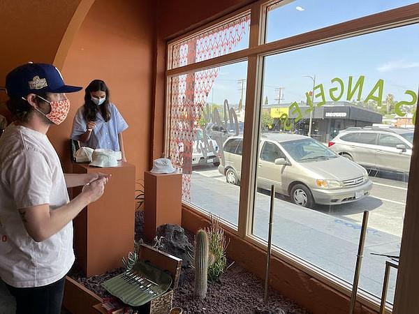 Ben Klevay works on Maison Kitsuné window. Also pictured, store director Sabrine Rivera.