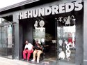 STREETWEAR HOME: The Hundreds boutique, 100 yards off of Los Angeles' Fairfax Avenue, is part of the concentration of stores making the thoroughfare a capital of streetwear style. At right is a worker at The Hundreds who gave his name as 5ive. Also pictured is 5ive's friend, who gave his name as Cali_Ant_Tay.