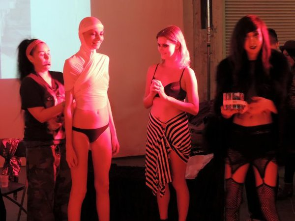 Katarina Lova, pictured center-left, being dressed up by an unidentified audience member in Bohemian Society's performance inspired fashion event. Taylor Dunn, a model, pictured right, and Lucas Logan, pictured far right.