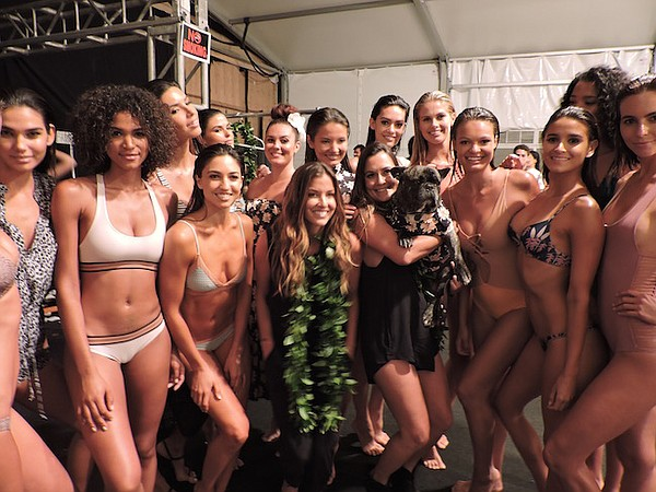 The Acacia Swimwear Post-Runway Show Pic;  Lyndie Irons, Acacia's co-owner, is wearing a green lei in the middle. Naomi Newirth, Acacia's designer and co-owner,  is holding a dog. Models from the label's July 19 runway show wear Acacia Swimwear.