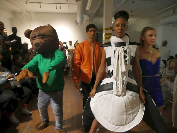 At finale of April 20 runway show, The B. James Experience, a woman dressed in a Shell Toe Adidas sneaker dress, center. Also a man dressed like D Bear, the B. James line's mascot.