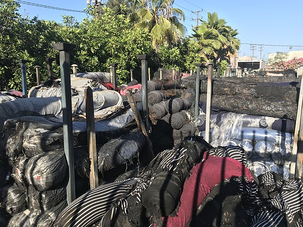Piles of charred fabric sit outside of Lavitex following a fire at the wholesaler's building.